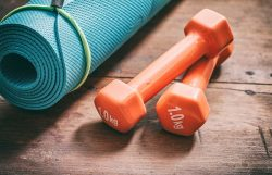 Green yoga mat and dumbbells on wooden background