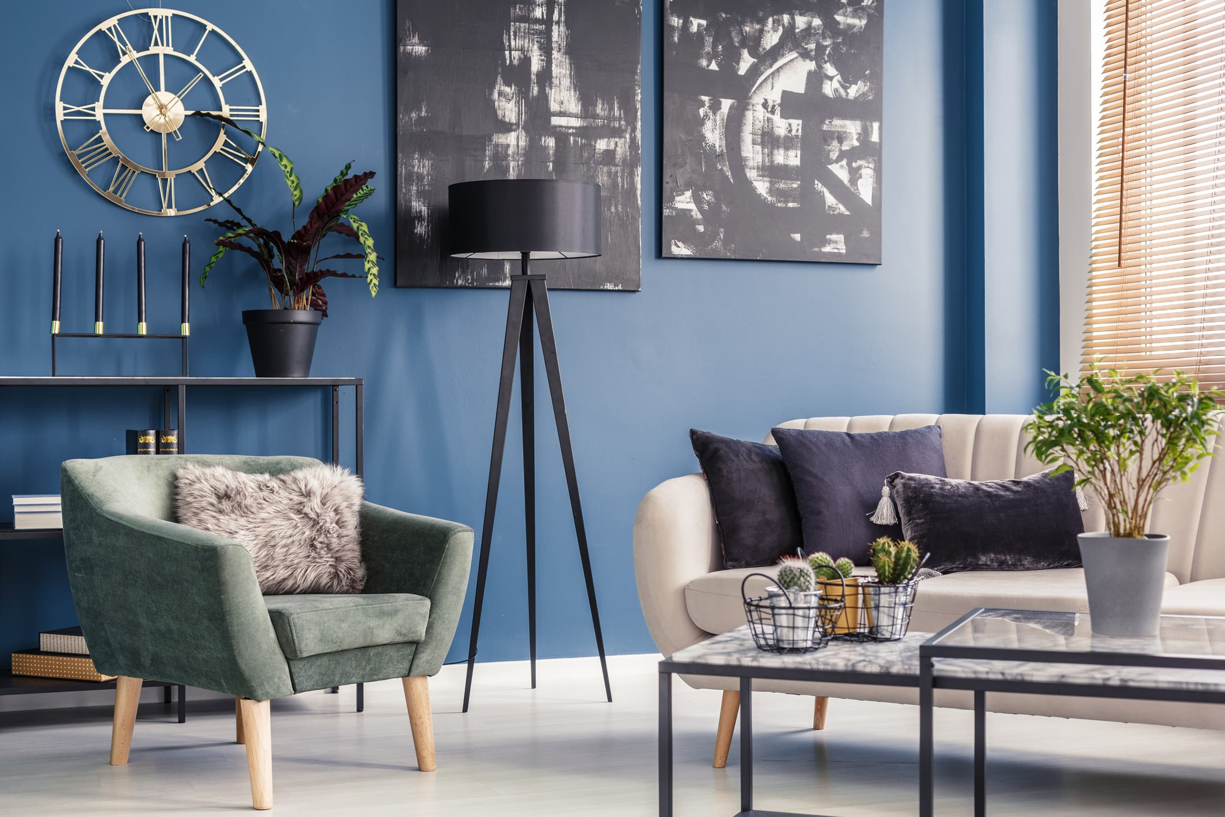 Elegant decorative cushions on a beige sofa and a modern mint green armchair in a blue living room interior